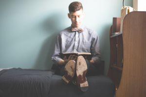 man die op zijn bed zit en een boek leest
