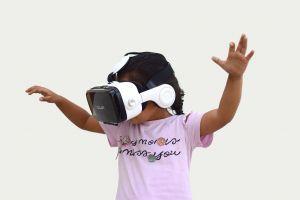 Een meisje met een VR-bril op haar hoofd. Ze is enthousiast.