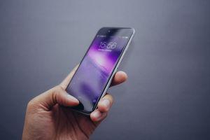 hand die een smartphone vast heeft
