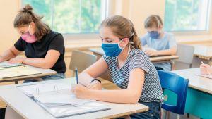 Leerlingen maken in de klas taken, met mondmasker aan