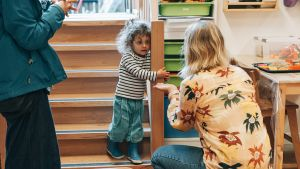 kindergarten teacher welcome a toddler in the classroom