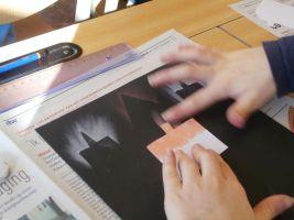 Kind werk met sjabloon en krijt op zwart tekenblad
