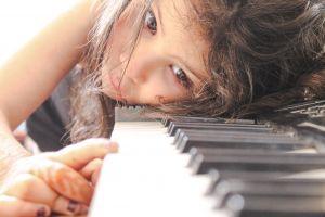 een kind met het hoofd op de piano