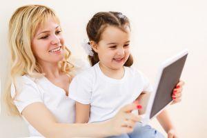 Een mama en haar dochtertje werken op een tablet.