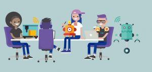 Mensen zitten rond een tafel. Op de tafel staat een robot en een laptop.