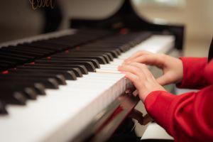 handen van een kind aan de piano