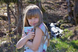 kind met boek in bos