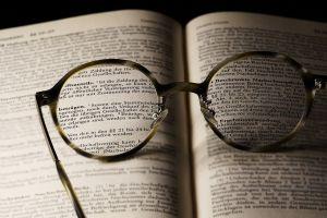 opengeslagen boek met een bril
