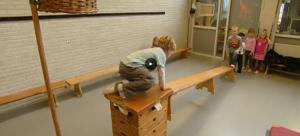Screenshot video met jongen die kruipt over een balk