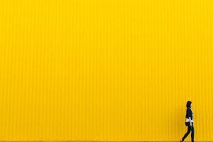 persoon die wandelt voor een gele muur