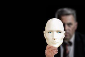 man houdt een masker vast
