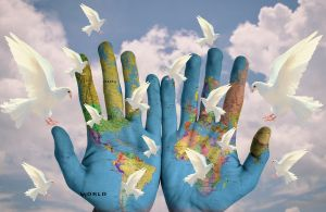 handen waarop de aarde is geschilderd, er vliegen witte duiven rond
