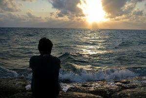 iemand die op het strand zit en naar de zee kijkt