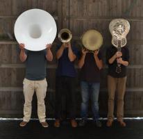 Vier mannen met voor hun gezichten muziekinstrumenten
