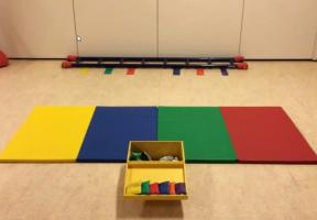 Gekleurde gymmatten en vakken met kleuren om iets te werpen