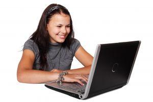 Een meisje zit achter haar computer.