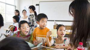Kinderen spreken met de juf in een klaslokaal