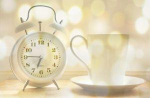 analoge klok naast een koffiekopje