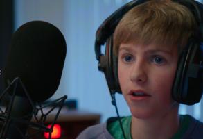 Jongen met koptelefoon op en microfoon