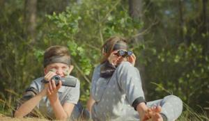Jongen en meisje in een bos, met camera en verrekijker
