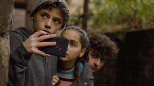 Drie jongeren die zich verstoppen achter een boom