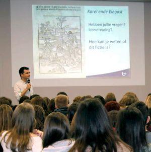 Prof. Remco Sleiderink geeft een gastcollege over 'Karel ende Elegast' op een middelbare school.