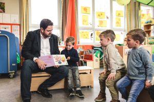 Een papa zit op een bankje in de klas en leest voor. Hij toont het boek aan drie kinderen.