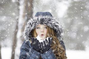 vrouw blaast sneeuw in haar handen weg
