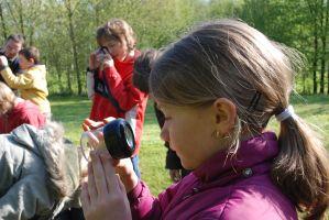 leerlingen kijken naar een kriebeldier in een potje