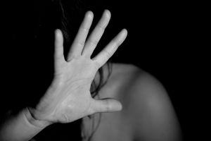 vrouw die haar hand omhoog houdt ter bescherming