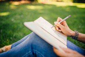 iemand zit op het gras en schrijft in een schrift