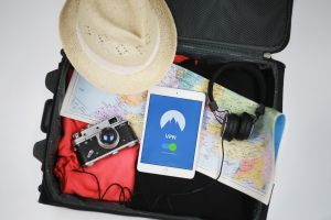 koffer met daarin een fototoestel, hoedje, kaart en koptelefoon