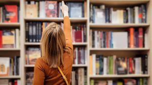 Mevrouw kiest een boek uit een boekenkast