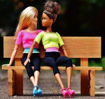 Twee barbiepoppen op een bankje