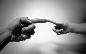 hand van een volwassene en een kid die elkaar raken