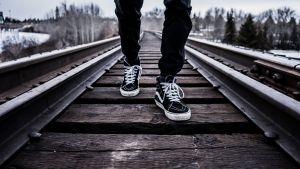 Man met sneakers op spoorweg