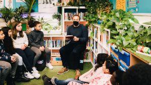 Een leraar leest voor uit een boek in de klas