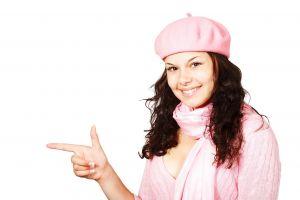 Meisje met roze baret en sjaal wijst naar iets buiten beeld
