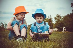 Twee kinderen met een hoedje lezen een boek