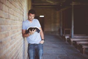 Jongeman leunt tegen een muur en leest een boek