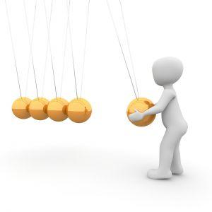 gouden balletjes hangen aan een koord, een manneke laat 1 bal bewegen
