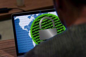Persoon achter laptop met een hangslot op het scherm