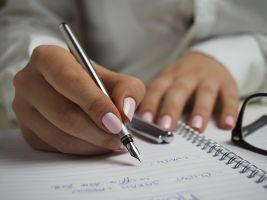 Hand die pen vasthoudt boven papier