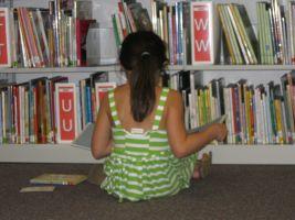 Meisje dat leest in boeken in bibliotheek
