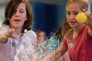 twee kinderen gooien een balletje in het water