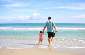 Father and daughter on the beach in the sea