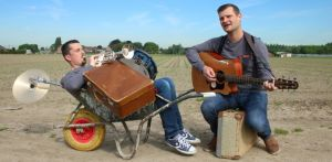 2 musicians of which 1 in a wheelbarrow