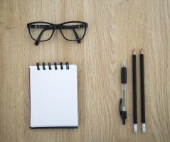 bureau met bril en schrijfmateriaal
