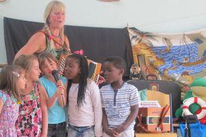 Hilde Frateur omgeven door kinderen