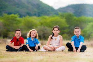 Vier kinderen zitten op het gras